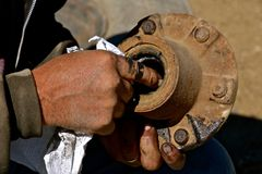 Greasy hands fixing bearing of a wheel and exle. Fingers filled with grease clean a ball bearing from a wheel and axle connection royalty free stock photo