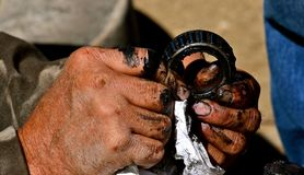 Greasy hands fixing bearing of a wheel and exle. Fingers filled with grease clean a ball bearing from a wheel and axle connection stock images