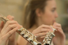 Fingers on flute with blurred face Stock Photos