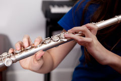 Fingers on a flute. Close up of a flautist playing a flute Royalty Free Stock Images
