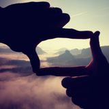 Fingers frame. Close up of hands making frame gesture. Blue misty valley bellow rocky peak. Sunny spring in rocky mountains. Stock Image