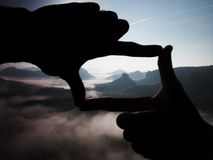 Fingers frame. Close up of hands making frame gesture. Blue misty valley bellow rocky peak. Sunny spring in rocky mountains. Stock Images