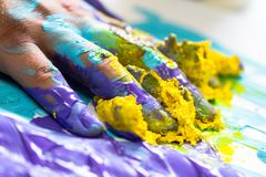 Fingers and hand dipped in colorful paint. As creativity and art concept, artist, painter, decorater, hobby, housework and abstract background Stock Photos