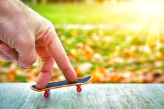 Fingers of hand skate on toy skateboard against green sunny background. concept of youth royalty free stock photos