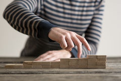 Fingers of a hand tracing out the ascent. Wooden dominos laid out on a table of gradually increasing height with the fingers of a hand tracing out the ascent Royalty Free Stock Photos