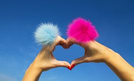 Fingers heart with blue and pink rings with fur on blue sky background royalty free stock image