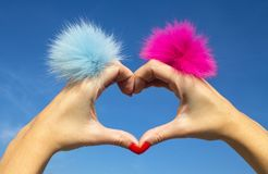 Fingers heart with blue and pink rings with fur on blue sky background stock images
