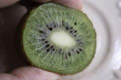 Fingers hold half a cut kiwi fruit royalty free stock photo