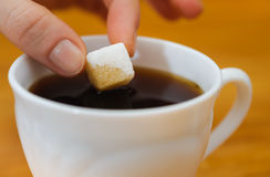 Fingers hold a lump sugar piece over cup of tea Stock Photos