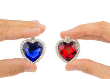 Fingers holding blue and red jewelry hearts Stock Image