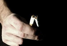 Fingers holding a broken cigarette Royalty Free Stock Photo