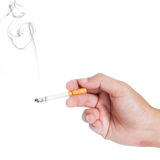 Fingers holding a cigarette with smoke. On white background Stock Photos
