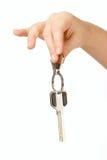 Fingers holding Golden key isolated over white Stock Photo