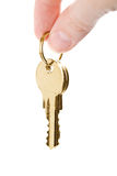Fingers holding golden keys isolated Stock Photography