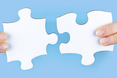 Fingers holding jigsaw puzzle pieces. Fingers joining large white blank jigsaw puzzle pieces Stock Photos
