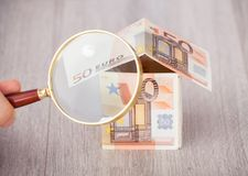 Fingers holding magnifying glass to analyze euro house Royalty Free Stock Photos