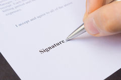Fingers holding pen writing signature Royalty Free Stock Photos