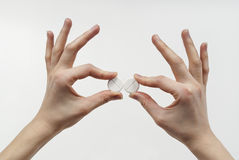 In the fingers holding pills Stock Image