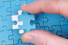 Fingers holding a puzzle piece Stock Images