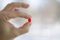 In fingers are holding a red pill. Blurred light background Royalty Free Stock Images