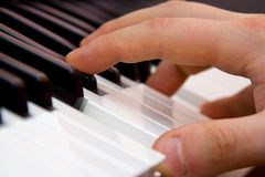 The fingers on the key of piano Stock Image