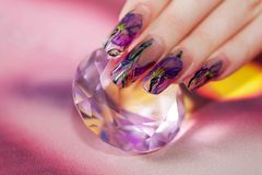 Fingers with  beautiful manicure touch a shining diamond Stock Images