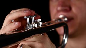 Fingers of man pushing button on trumpet. Black background studio stock video footage