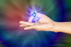 Fingers on a meditation position. With blue light beams and dynamic colorful background Royalty Free Stock Photos