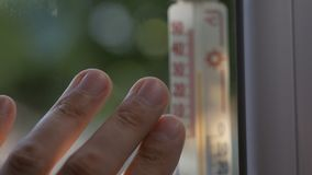 Fingers men touch the window, which is attached to a mercury thermometer showing the temperature outside 32 degrees