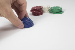 Fingers moving pile of blue poker chips Royalty Free Stock Images