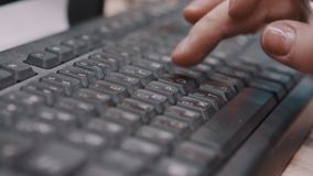 Fingers of office worker typing on keyboard and holding pen. Fingers of office worker typing on keyboard with cyrillic letters inscriptions and holding pen stock video