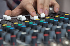 Fingers operating sound console Stock Photos