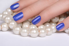 Fingers on pearls. Close-up of female hand covering a pearl neck Royalty Free Stock Image