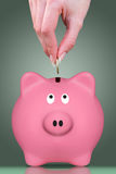 Fingers and piggy bank Royalty Free Stock Images
