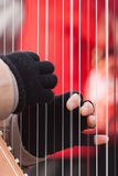 Fingers pinching strings on harp in Montmartre Royalty Free Stock Photos