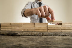 Fingers placing wooden block on orderly stack. With unidentifiable man in necktie in background royalty free stock image