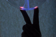 Fingers and plasma. In the background is the hand that was illuminated by plasma from plasma lamp stock photo