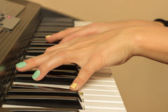 Fingers playing electronic piano keyboards Stock Photos