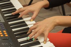 Fingers playing electronic piano keyboards. Beautiful female fingers playing electronic piano keyboards in the music studio Stock Images