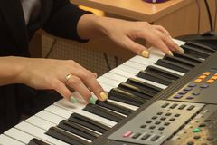 Fingers playing electronic piano keyboards. Beautiful female fingers playing electronic piano or synthesizer keyboards in the music studio Royalty Free Stock Photography