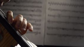 Fingers playing the strings of a cello in the background sheets with notes. Close up. Side view. Fingers playing the strings of a cello musical instrument in the stock video footage
