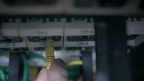The fingers pluging the Ethernet cable into the patch panel. stock footage