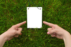Fingers point to paper note. White sheet and woman`s hands. Paper for your simple text. Green grass is background. Fingers point to note Royalty Free Stock Images