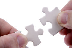 Fingers and puzzle pieces Stock Photography