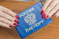 Fingers with red and black manicure holding a passport Royalty Free Stock Photo
