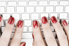 Fingers with red nail. Typing on keyboard Stock Photo