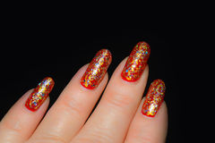 Fingers with red nail polish with silver and gold tinsel. On a black background Stock Images