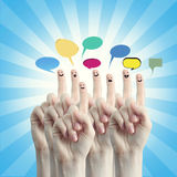 Fingers representing a social network. Happy group of finger smileys with social chat sign and speech bubbles Stock Photos