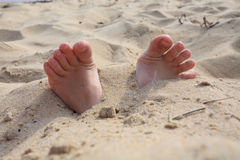 Fingers from sand. Children's feet are buried in sand stock photos