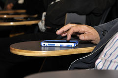 Fingers on smart-phone. An attendee in a session occupy himself with his smart-phone Royalty Free Stock Photography